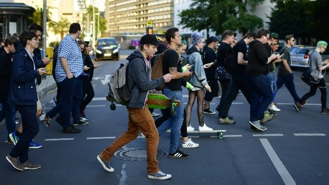 Pessoas atravessando a rua com seus smartphones